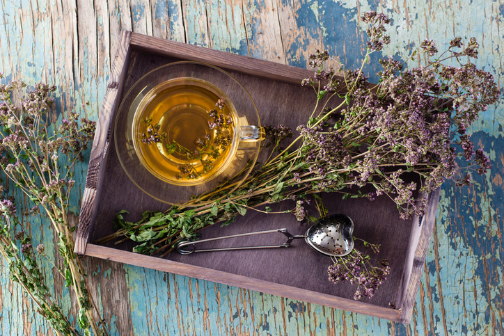 Herbal treatment. Tea with oregano and a bunch of herbs in a wooden tray on the table. Top view